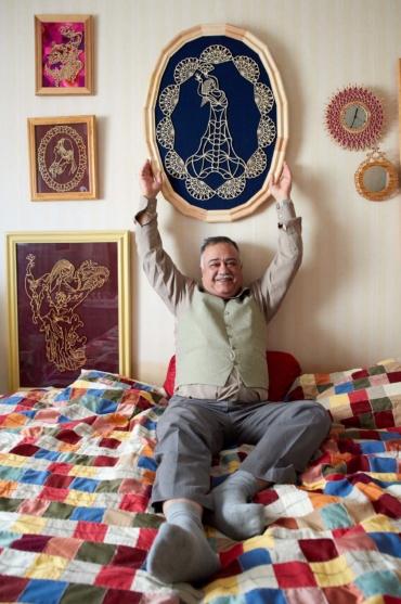 Ahmad Seddigh sitter på sängen med flera plywoodtavlor på vägen ovanför sig.