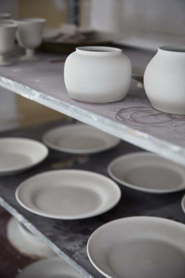 Färdiga skålar och tallrikar står på tork.